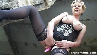 Sexy old dame in stockings and corset is toying pussy in an abandoned building